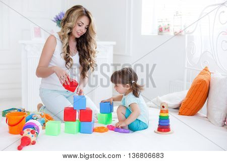 Beautiful young mother,with long blonde curly hair ,playing with his little daughter in a logical educational games,pyramid and collect the colored blocks,the daughter is a brunette girl with two ponytails on her head