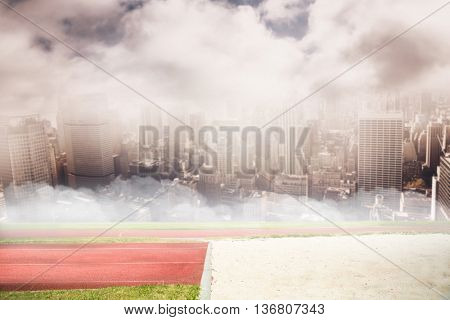 View of running track against aerial view of a city on a cloudy day