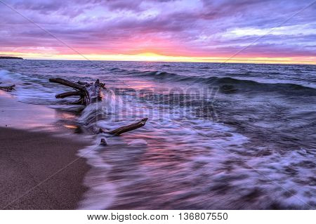 Driftwood Beach. Driftwood surrounded by waves set against a sunset sky. Port Crescent State Park. Port Austin, Michigan.