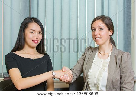 Two Business Woman Shaking Hands By The Computer