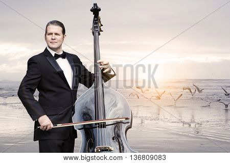 man in tuxedo playing the doublebass standing by the ocean