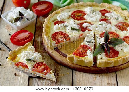 A Classic Quiche Lorraine Pie With Soft Feta Cheese And Tomatoes In A Baking Dish On A Table In A Ru