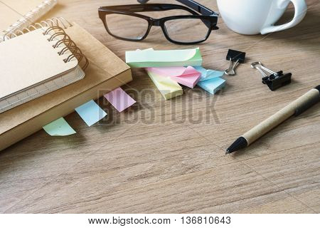 Cup of coffee with blank notebook and notepaper on wooden desk and copy space