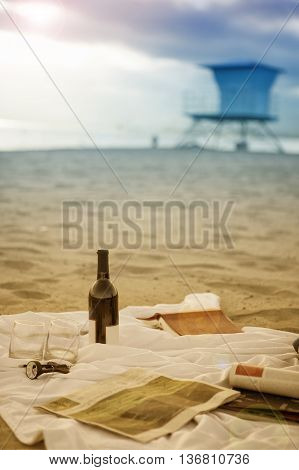 picnic blanket on beach with wine glasses and book