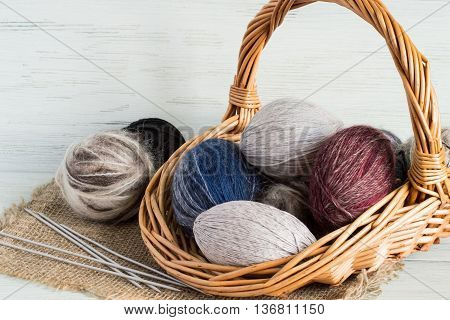 Balls wool yarn in a wicker basket and knitting needles on a burlap on a light wooden background.