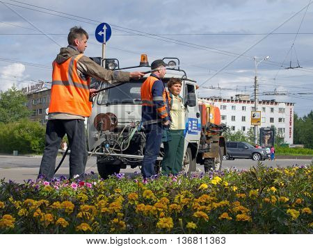 Murmansk, Russia - June 21, 2013, Employees of urban utilities watering the lawn on the square in the city of Murmansk