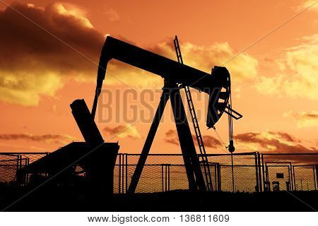 oil rig pumping on cloudy sky background at dusk