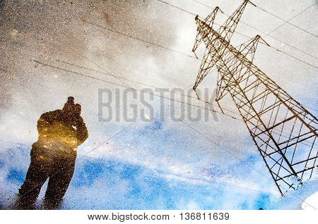 Photographer reflection on a water puddle with blue sky and electric tower