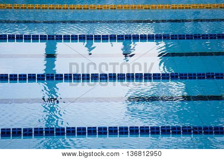 swimming pool detail with blue water and plastic lanes