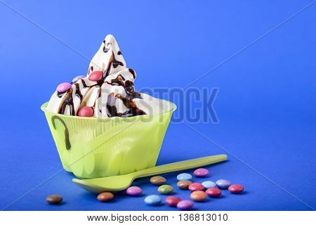 frozen yogurt with chocolate and chocolate candy topping on blue background with green spoon and chocolate candy