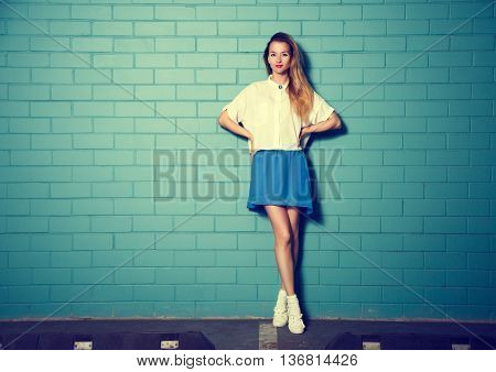 Full Length Portrait of Trendy Hipster Girl Standing at the Turquoise Brick Wall Background. Urban Fashion Concept. Toned Photo with Copy Space.