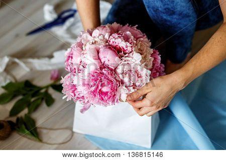 Florist making a bouguet of peonies in kraft paper bag - workshop
