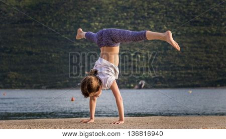 The young girl engaged in acrobatics fun on the pier