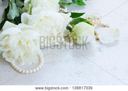 White fresh peony flowers bouquet with pearls jewellery strand on white wooden table