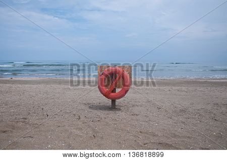 red life buoy attached to a pole on the beach