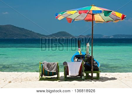 Beach umbrella chairs and boat in Komodo beach in Coral island Thailand