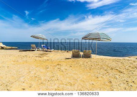 Sun loungers on a beach underneath a parasol