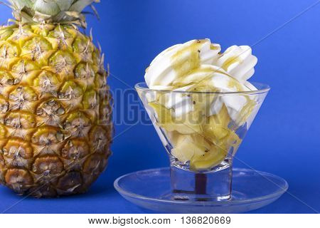 frozen yogurt with kiwi topping and pineapple in glass bowl on blue background with pineapple
