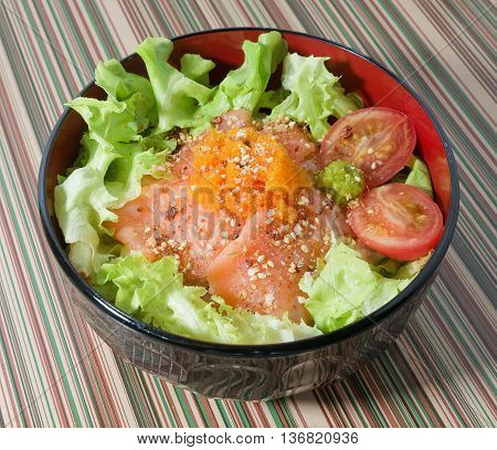 Japanese Cuisine White Steamed Rice Topping with Fresh Salmon Tomaroes and Green Lettuce in Donburi Bowl.