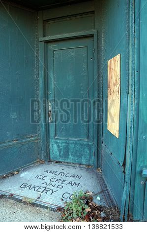 JOLIET, ILLINOIS / UNITED STATES - NOVEMBER 1, 2015: The front door and threshold of the building of the former American Ice Cream & Bakery Company, now boarded up near downtown Joliet.