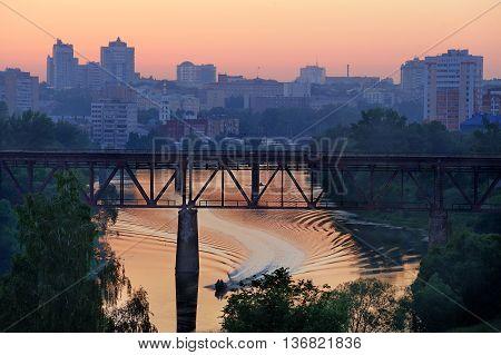 Railway bridge the bridge over the river boat racing at twilight horizontal