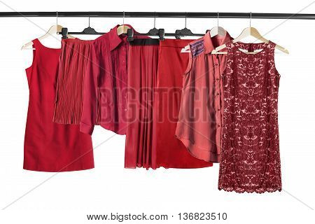 Group of red clothes on clothes racks isolated over white
