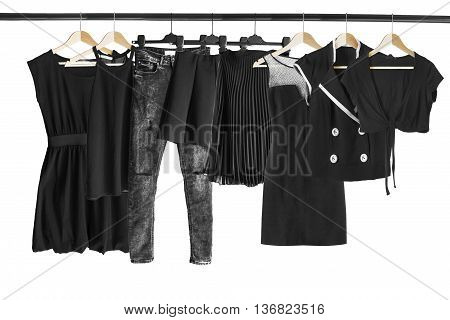 Group of black clothes hanging on clothes racks isolated over white