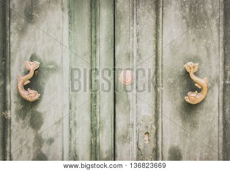 A Pair of Old Dolphin Shaped Metal Knockers on Green Wooden Distressed Doors in Mdina Malta