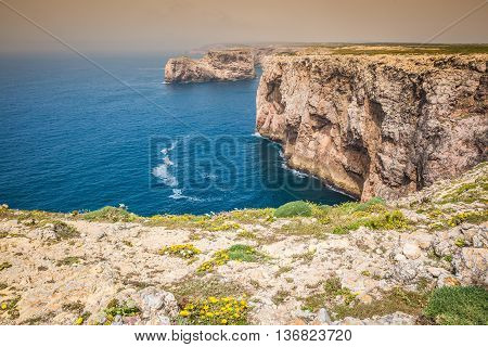 High cliffs and blue ocean at Cabo Sao Vicente on coast of Portugal