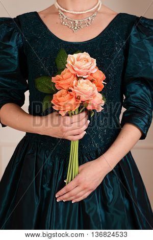 closeup Victorian woman holding roses wearing diamond necklace