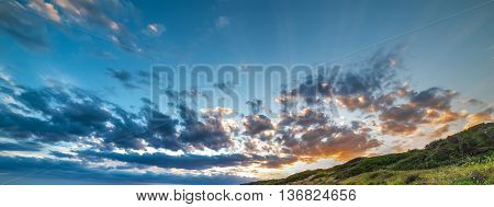 green hill under a colorful sky at sunset