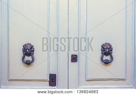 A Pair of Old Metal Lion Head Knockers on Light Blue Doors in Mdina Malta