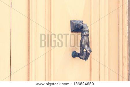 Hand shaped Metal Knocker on Beige Wooden door Malta