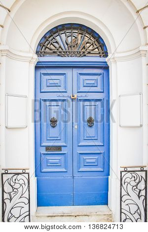 Blue Wooden Doors with Black Metal Knockers and two Empty White Boards from Both Sides for Your text Malta