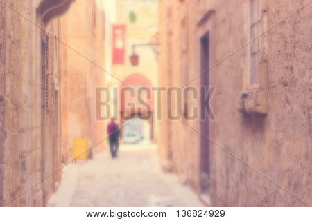 Defocused Background with Man walking down the Ancient narrow Street in Mdina Malta. Warm color filter used