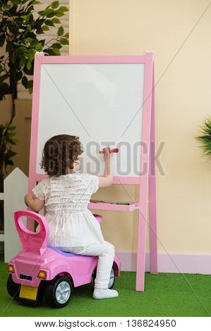 little girl writing on the drawing board