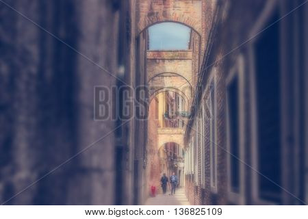 Defocused Background with two Men walking down the Ancient narrow Street of Venice Italy. Instagram style filter used