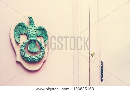 A Pair of Old Metal Empire Style Eagle Knockers on Wooden Pink Door in Mdina Malta. Space for your text