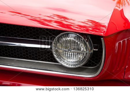 Headlight Of A Oldtimer Red Car In The Street