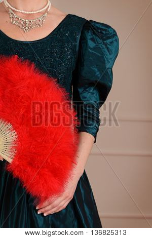 closeup of vintage woman holding red feather fan