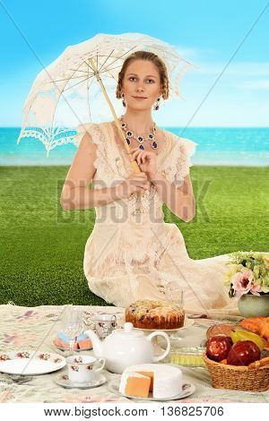 young edwardian woman at picnic with umbrella