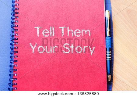 Tell them your story text concept write on notebook