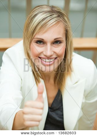 Businesswoman smiling with her thumb up in an office