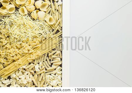 Mixed dried pasta selection surrounding white board and dividing photo in a half. Space for your text. Top view shot