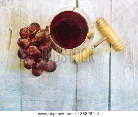 A photo of a glass of red wine with a bunch of grapes and an old wooden corkscrew shot from above on a light blue wooden background texture with copyspace and a textured effect