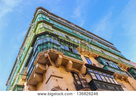 Corner of the house with rows of colorful balconies in Valletta Malta