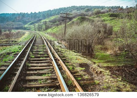 The train railway turns upleft in summer landscape