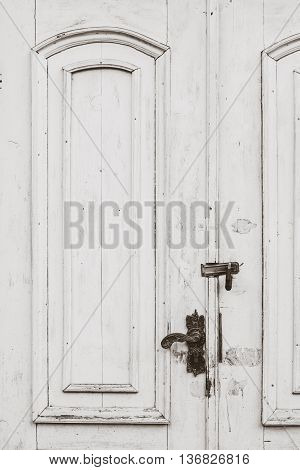 Old distressed white doors close up with black metal handle and lock. Vertical composition