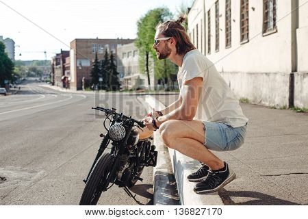 portrait young guy with a beard and mustache with sunglasses posing on the street vintage man fashion men hipster street casual motorcycle