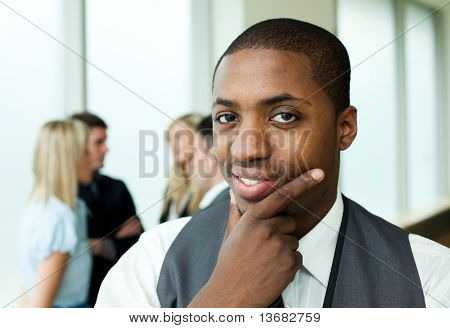 Thoughtful ethnic businessman in office smiling at the camera